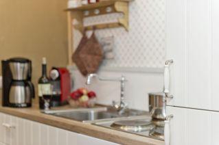 die kleine Küchenzeile verfügt über Kühlschrank, Backofen und Herd, Kaffeemaschine, Toaster und Wasserkocher